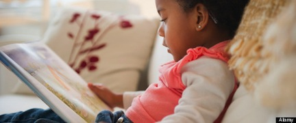 Black girl reading book on sofa